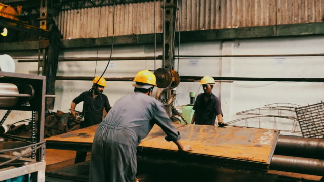 team of steel factory worker using a crane to lower the steel plates - industria metallurgica video stock e b–roll