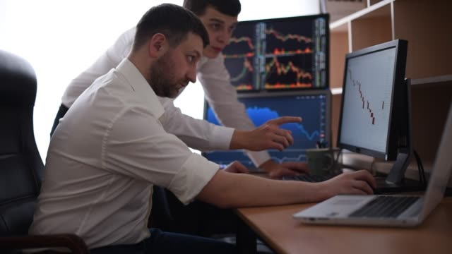 vídeos de stock e filmes b-roll de team of stockbrokers are having a conversation in a dark office with display screens. stock exchange trading forex finance graphic concept. businessmen trading stocks online - criar laços