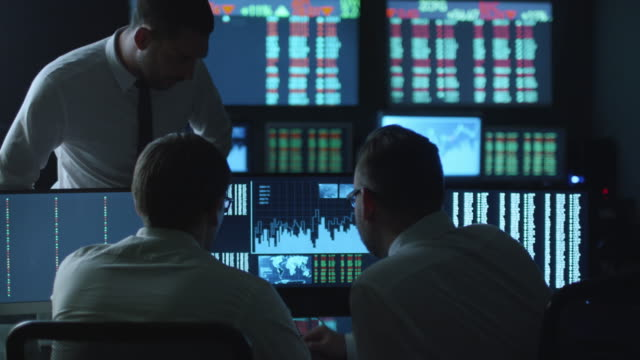 team of stockbrokers are having a conversation in a dark office with display screens. - stock broker stock videos & royalty-free footage