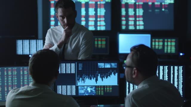 Équipe des courtiers sont avoir une conversation dans un bureau noir avec écrans d'affichage. - Vidéo