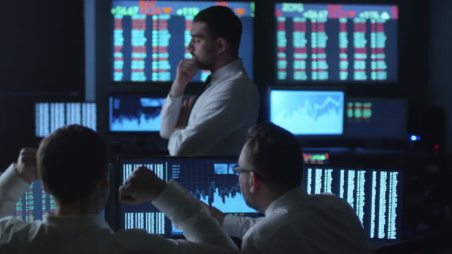 Team of successful stockbrokers celebrate reached goals in dark office with display screens. video