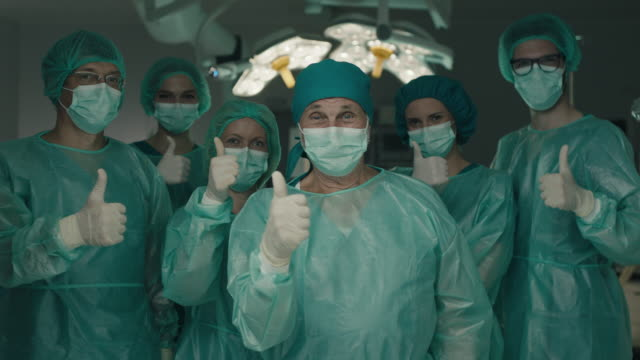 team of surgeons in operating room showing thumbs up - mask filmów i materiałów b-roll