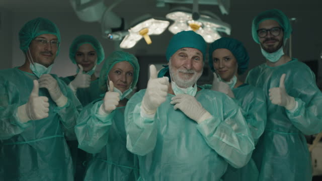 Team of surgeons in operating room showing thumbs up Team of surgeons in operating room showing thumbs up and looking at camera in operating room physical position stock videos & royalty-free footage