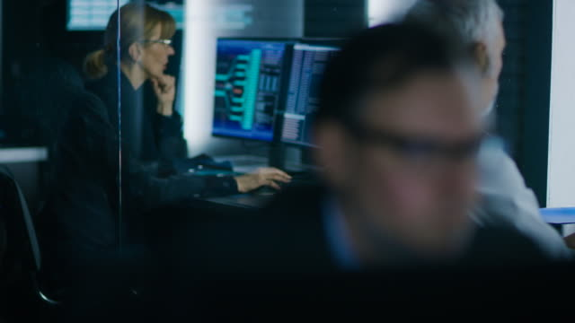 team of technical specialists working on personal computers at their workstations in the system control room. - quartiere generale video stock e b–roll