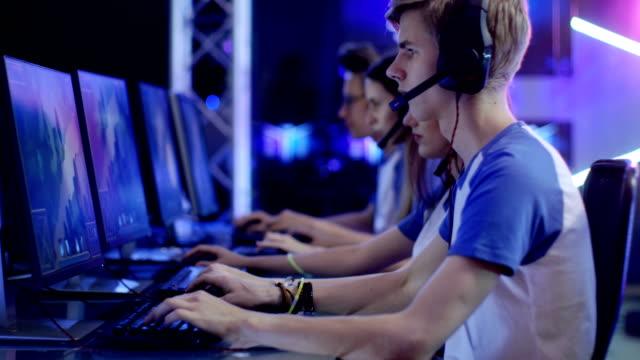 esport トーナメントで 10 代のゲーマー再生 mmorpg ゲームでのチーム。美しいゲームを表示する、プレイヤーはヘッドセット マイクに向かって話すし、勝つのために積極的に遊ぶ。 - ゲーム ヘッドフォン点の映像素材/bロール