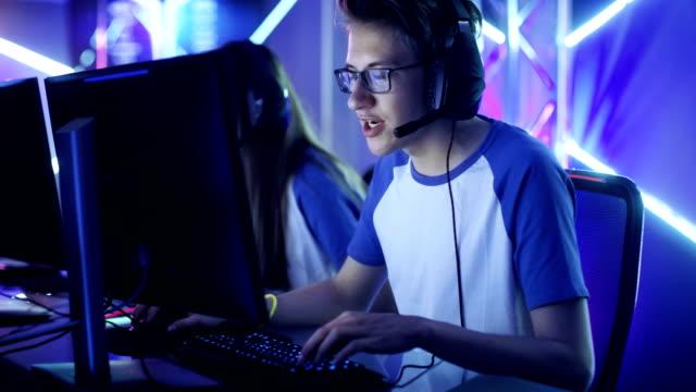 esport トーナメントで 10 代ゲーマー プレイで多人数参加型の pc ゲームのチーム。感情的なゲームの瞬間。 - ゲーム ヘッドフォン点の映像素材/bロール
