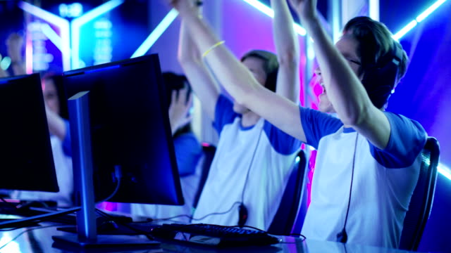 Team of Teenage Gamers Win Internet Cafe Online Video Gaming Tournament and Celebrate with High-Fives.