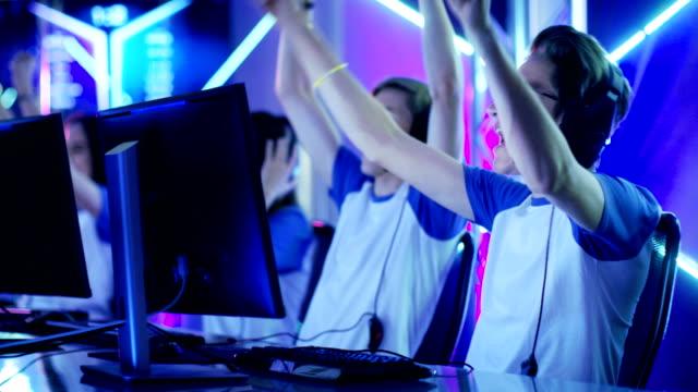 team aus jugendlichen spielern gewinnen internet cafe online-video-gaming-turnier und feiern sie mit high-fives. - computerspieler stock-videos und b-roll-filmmaterial