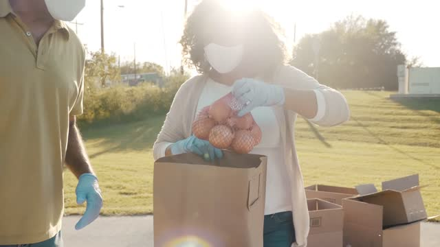 vídeos y material grabado en eventos de stock de equipo de voluntarios que ensamblan alimentos donados durante la conducción de alimentos - food drive