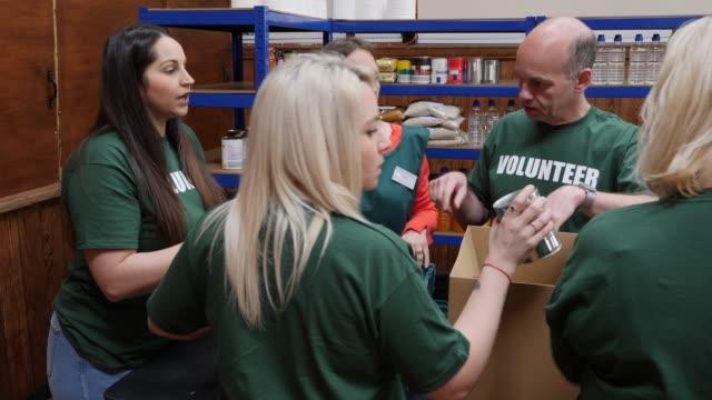 vídeos de stock, filmes e b-roll de 4k: equipe de voluntários, classificação de alimentos em caixas em um banco de alimentos - voluntário