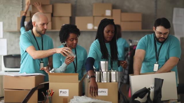 지역사회를 위해 함께 일하는 자원봉사자 팀 - giving tuesday 스톡 비디오 및 b-롤 화면