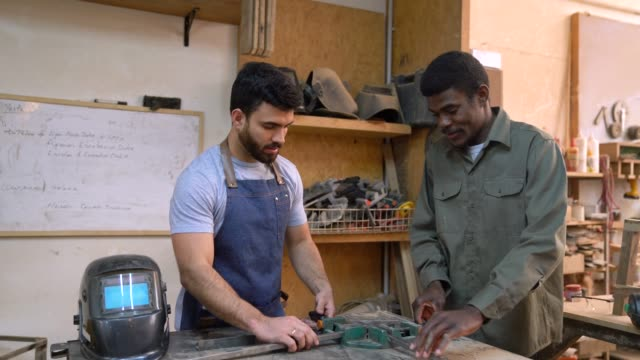 Team of welders at a workshop adjusting metal bars talking and then facing camera smiling