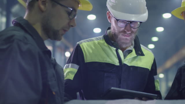 Team of workers at a heavy industry factory have a conversation while looking at a blueprint. Team of workers at a heavy industry factory have a conversation while looking at a blueprint. construction equipment stock videos & royalty-free footage
