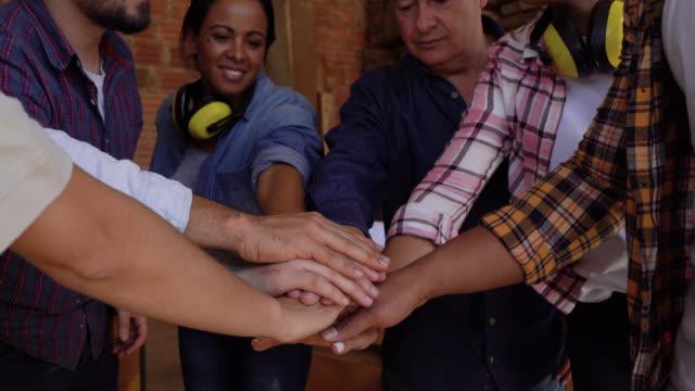 stockvideo's en b-roll-footage met team van arbeiders in een houtfabriek allemaal met handen in het vieren en doen van hoge vijf - huddle