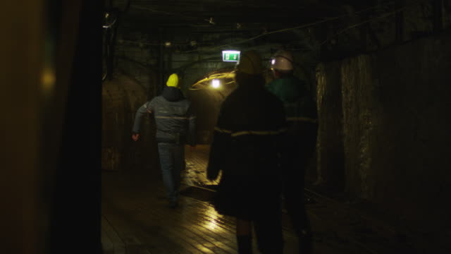 Team of Workers in Hard Hats are Walking in Mining Tunnel video