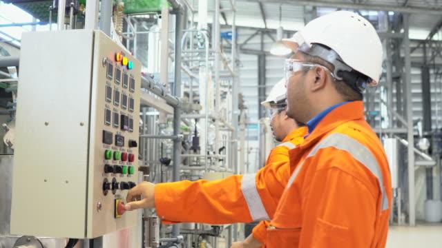 vídeos y material grabado en eventos de stock de equipo de trabajadores caminando y discutiendo en plan de combustible antecedentes industriales - material de construcción