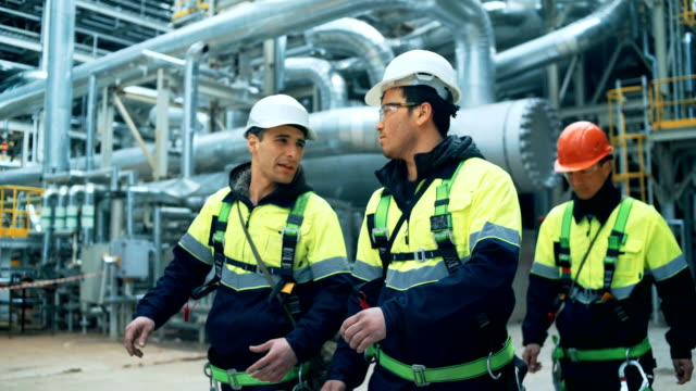 Team of workers walking on fuel plant