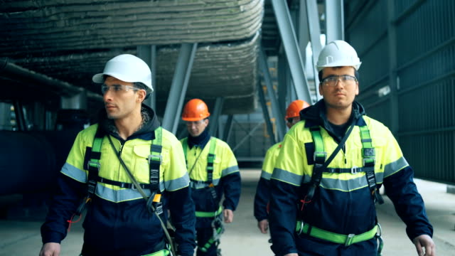 Team of workers walking on industrial plant