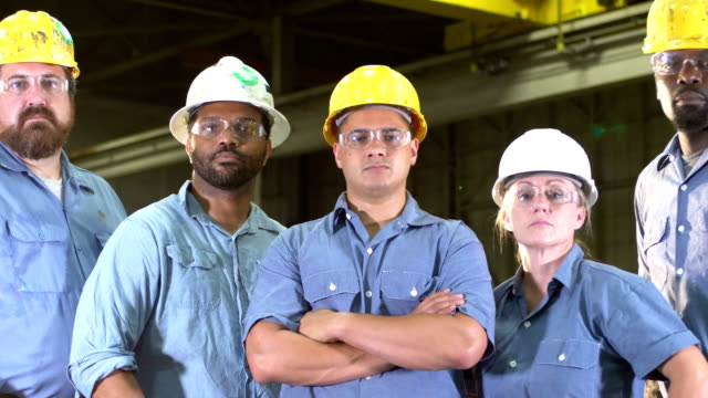 Team of workers with hard hats, safety glasses, serious Team of five multi-ethnic workers in a metal fabrication plant, wearing hard hats and safety glasses, staring at the camera with serious expressions. One is a mature woman in her 40s with hands on her hips. manufacturing occupation stock videos & royalty-free footage