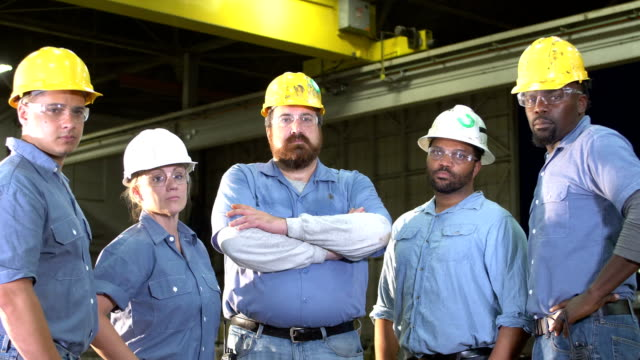 team of workers with hard hats, safety glasses, serious - irriducibilità video stock e b–roll