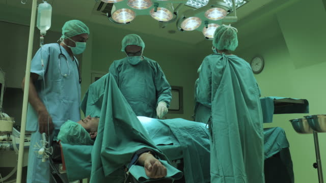Team of worried surgeons talking about patient's health problems before a surgery. video