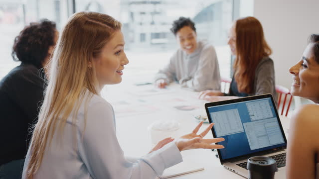vídeos de stock e filmes b-roll de team of young businesswomen with laptop meeting around table in modern workspace - coworking