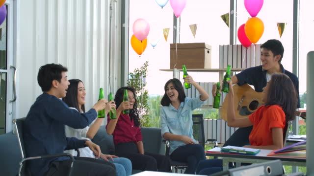 トーストと彼らのオフィスで眼鏡を調達をチャリンと若者踊っていて楽しいチームを祝います。スローモーション撮影 - 飲み会点の映像素材/bロール