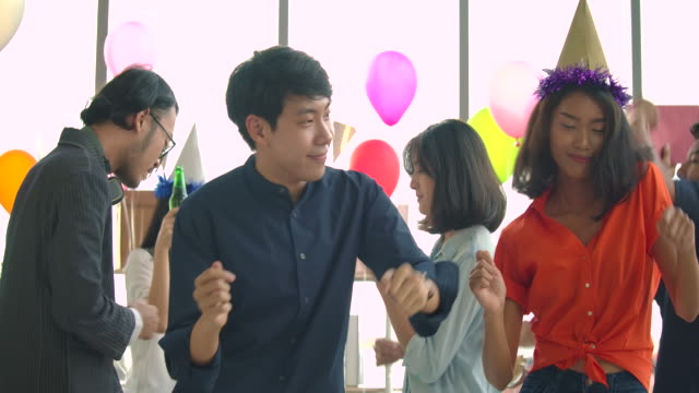 team of young people dancing and having fun celebrate with toast and clinking raising glasses in their office. slow motion shot - office party stock videos and b-roll footage