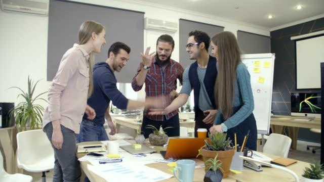teamet sätter händerna ihop och höjer armarna upp - kommunikationssätt bildbanksvideor och videomaterial från bakom kulisserna
