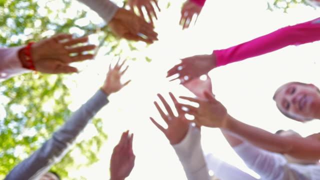 vídeos de stock e filmes b-roll de equipa atingir no huddle em comemoração antes de corrida de competição de consciencialização contra o cancro da mama - benefits