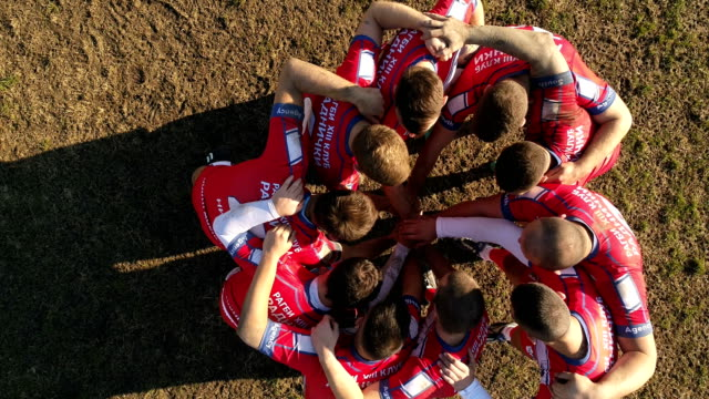 Team spirit Young and strong rugby team on the field, holding hands all together, aerial view. rugby stock videos & royalty-free footage