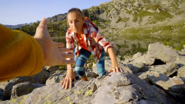 Teammate helping hiker to reach summit . Couple hiking in Switzerland, hand reach out to help female hiker reach the summit. A helping hand concept