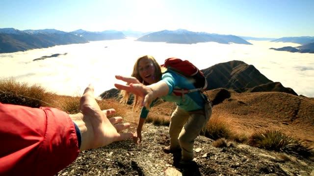 Teammate helping hiker to reach summit video