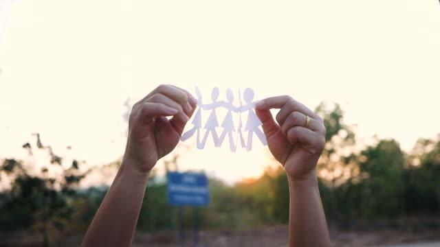 日没の背景を越えて公園で手をつないでいる人々のペーパーチェーングループとチームワークのコンセプト。 - community activism点の映像素材/bロール