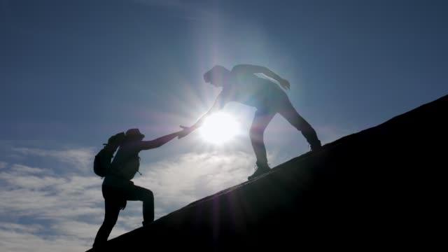 teamwork vandrare hjälp att ge en hjälpande hand till varandra för att klättra mountain - assistans bildbanksvideor och videomaterial från bakom kulisserna