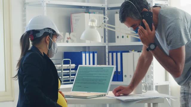 lavoro di squadra in una nuova configurazione dell'ufficio. co-working su un progetto aziendale durante la pandemia di covid-19. brainstorming. due colleghi che indossano maschere protettive per il viso al lavoro per appiattire la curva - potere femminile video stock e b–roll