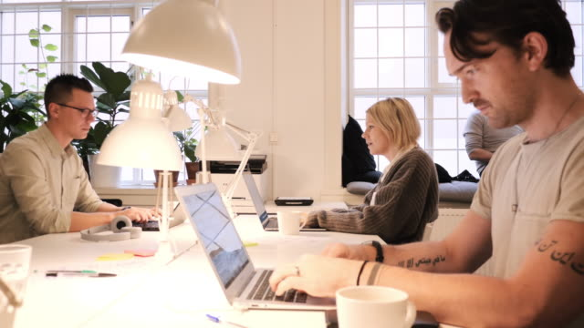 vídeos y material grabado en eventos de stock de trabajo en equipo en el espacio de coworking moderno - grupo multiétnico de profesionales que trabajan juntos - trabajo freelance