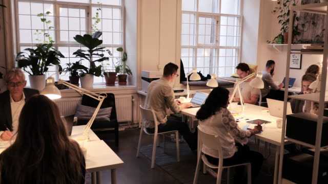 teamwork im modernen coworking space - multi-ethnische gruppe von fachleuten, die zusammenarbeiten - freischaffender stock-videos und b-roll-filmmaterial