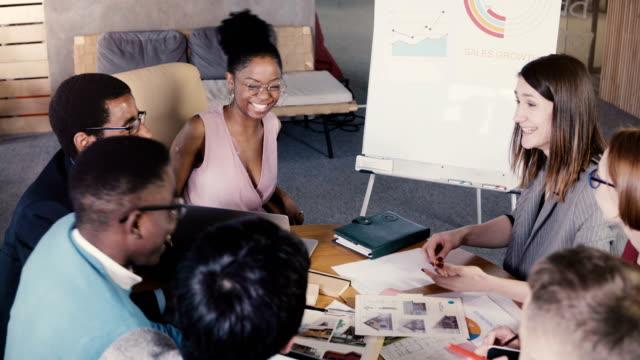 teamarbeit im trendigen loft geschäft coworking space. glücklich multiethnischen kreative nachwuchskräfte brainstorming zusammen 4k - reisebüro stock-videos und b-roll-filmmaterial