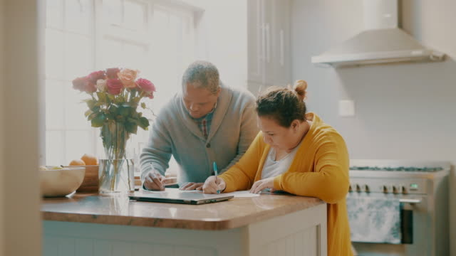 Teamwork makes tax season work 4k video footage of a mature couple going through paperwork together at home form filling stock videos & royalty-free footage