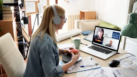 Teamwork over the video call - employees using teleconference Mature woman working from home on laptop. Woman has blueprints on the table, dealing with investments and finances coworker stock videos & royalty-free footage