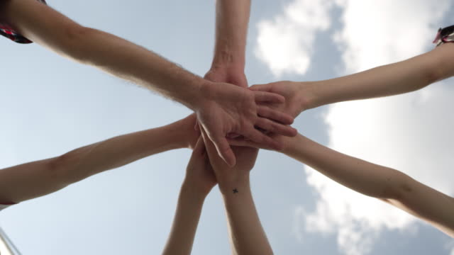 Teamwork - team putting their hands together video