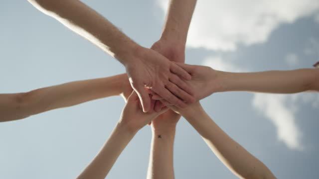 Teamwork - team putting their hands together video