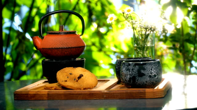 Teapot and Tea Cups With Cookies Outdoors