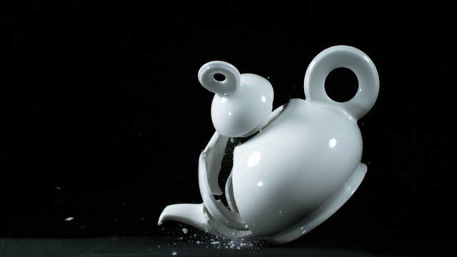 tea-pot falling and exploding on black background, slow motion 4k - teapot stock videos & royalty-free footage