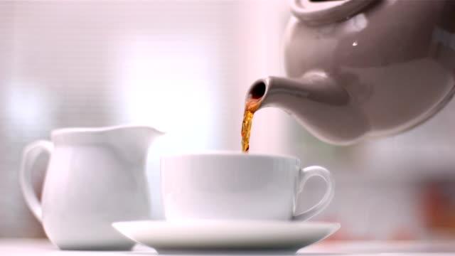 teekanne mit tasse tee eingießen - milchkrug stock-videos und b-roll-filmmaterial