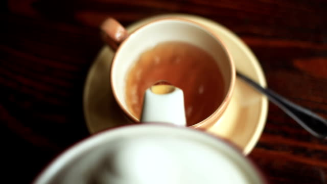 Teapot pouring tea into Cup pour tea into a Cup from the kettle hd format stock videos & royalty-free footage
