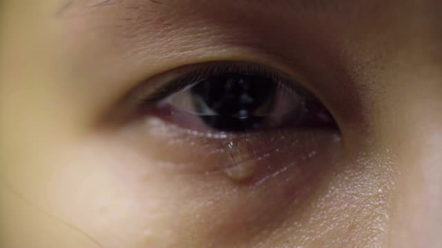 CLOSE UP: Tear comes out of an eye and streaks down the cheek. Sad abused female with brown eyes crying , Asian Model. video