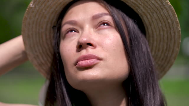 Tears flow on the cheek of asian girl in a summer hat. She is grieve. Close up.