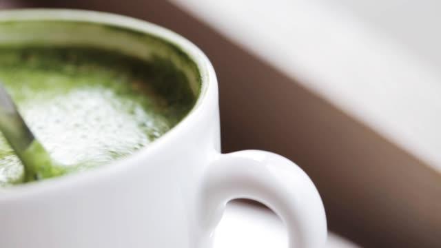 teelöffel matcha grünen tee latte cup rühren - milchkaffee stock-videos und b-roll-filmmaterial